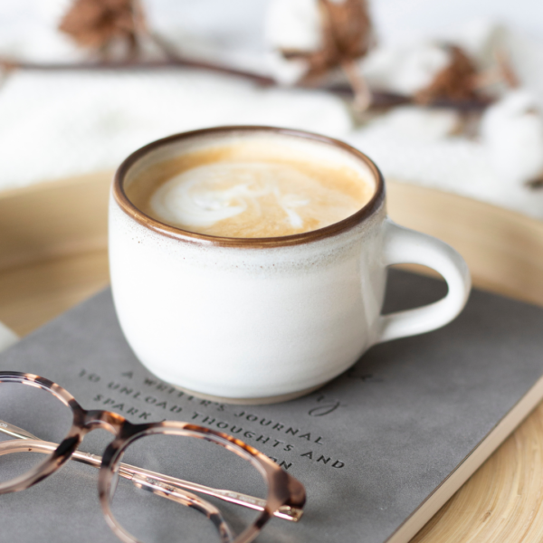 A handmade short, gently rounded mug with a shiny white glaze and a brown rim