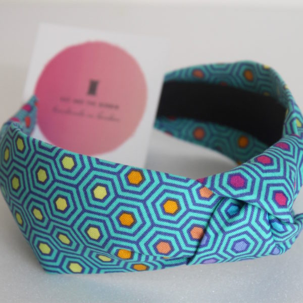 Handmade knotted heaband in bright teal and rainbow hexagon detail