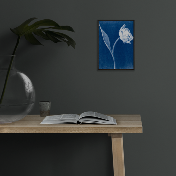 Double tulip art print in deep blue. Framed in black hanging on a wall above a table.