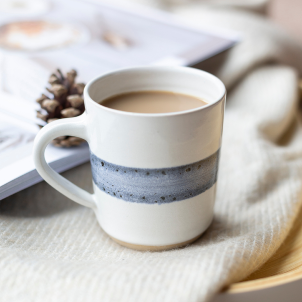 A handmade, wheel thrown mug. Shiny white glaze with a band of blue running around the middle of the mug.