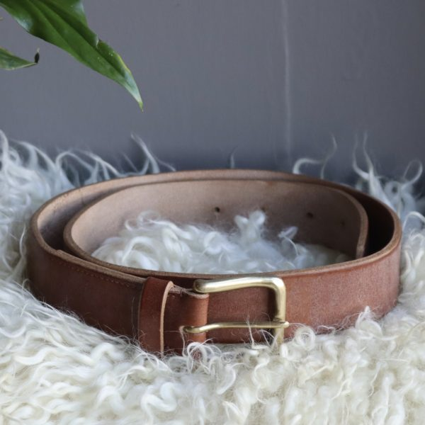 Hand stitched, oak bark tanned leather belt with a brass buckle.