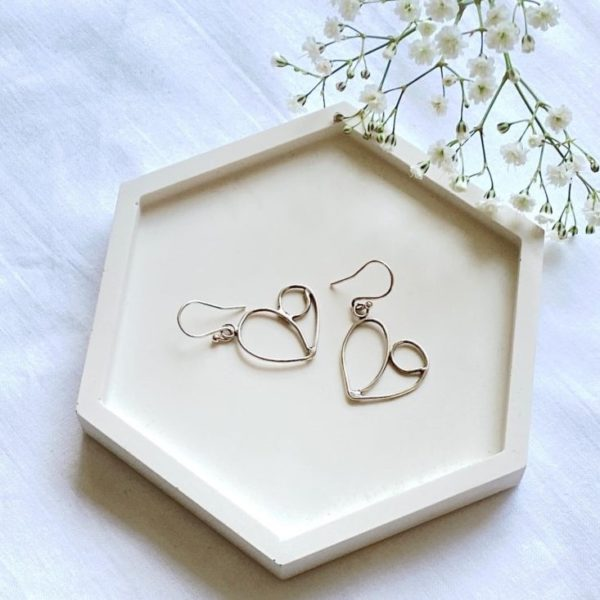 Handmade Cyprien Love and Hope silver earrings with hand scrolled polished dainty hearts that dangle from the earring hooks