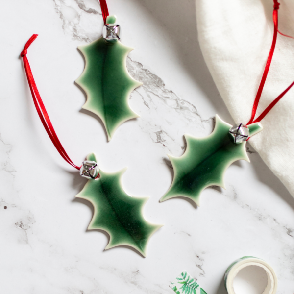 A shiny green porcelain holly leaf hanging decoration with a bright red ribbon and a silver bell