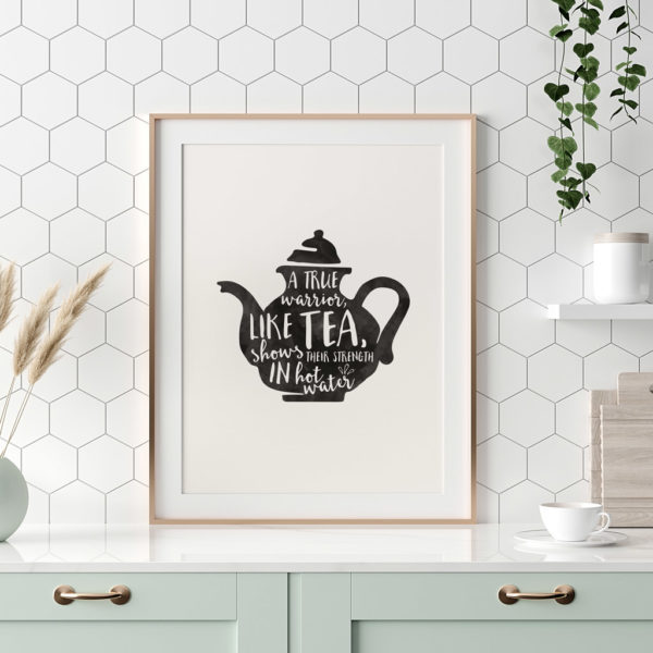 An off white and black print. A true warrior, like tea, shows his/her/their strength in hot water.